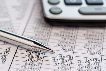 tax return: a calculator is on a balance sheet numbers are statistics. photo icon for sales, profit and cost.