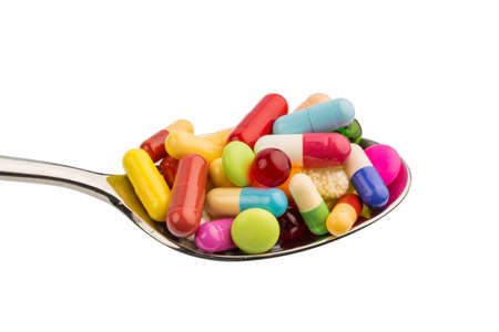 investigated: many colorful pills on a spoon. symbol photo for tablets addiction and abuse of drugs.