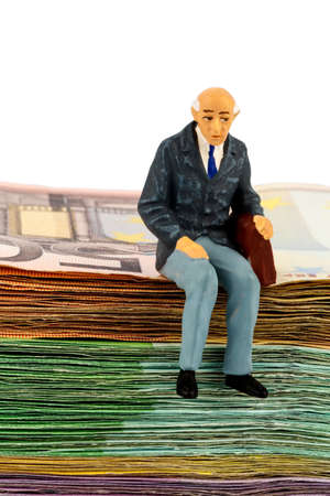basic scheme: symbol photo for retirement and old age, figure of an old man sitting on a stack of bills