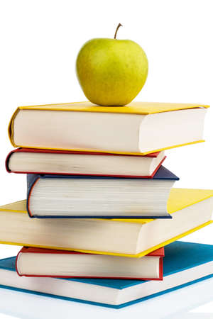 vitamin rich: an apple lying on a pile of books. symbol photo for healthy and vitamin rich food in the school break.