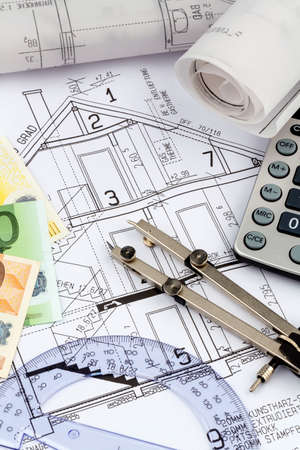 an architects blueprint with a calculator and euro money. symbol photo for financing and planning of a new home. photo