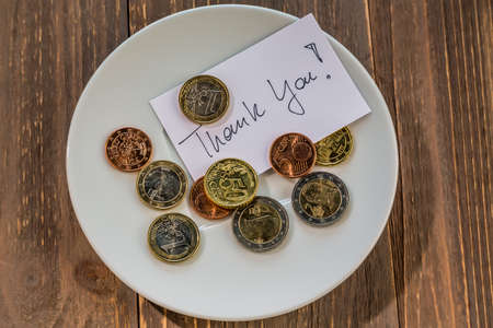 tax tips: a plate of coins for tipping or charge for toilets. in english