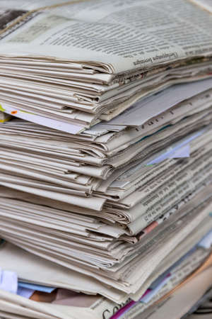 wastepaper: a stack of old newspapers ready for removal by waste paper disposal Editorial