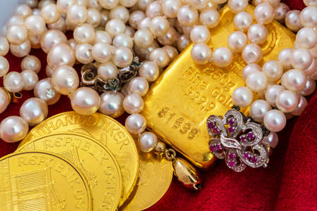 tangible: gold coins and bars with decorations on red velvet. symbol photo of wealth, luxury, wealth tax.