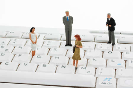 peoplesoft: several figures of business people standing on a computer keyboard