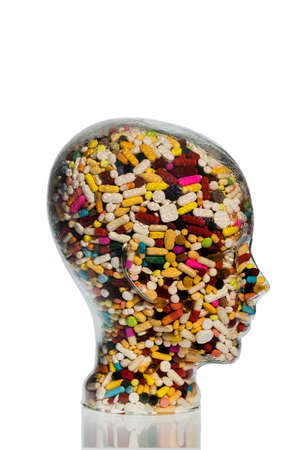 supplementary: a head made of glass filled with many tablets. photo icon for drugs, abuse and addiction tablets. Stock Photo