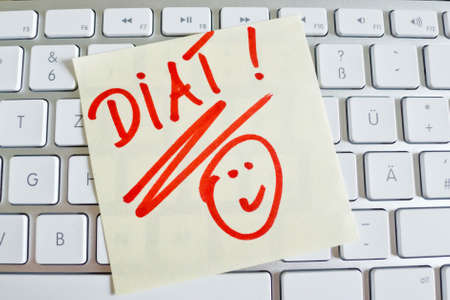 thinness: a sticky note is on the keyboard of a computer reminder: diet Stock Photo