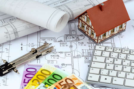 an architects blueprint with euro money. symbol photo for financing and planning of a new home. photo