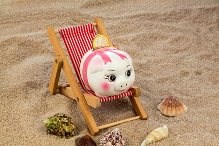 beach chair with euro currency on the sandy beach. symbol photo for costs in travel, vacation, holidays. save on vacation photo