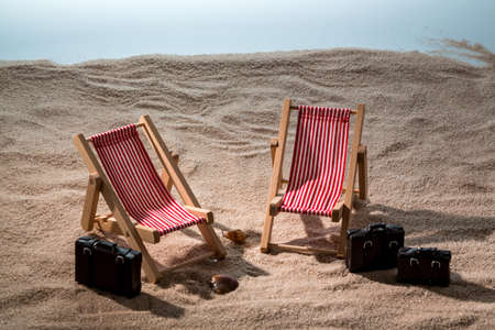 save time: kkleine deck chairs on the sandy beach with suitcase Stock Photo