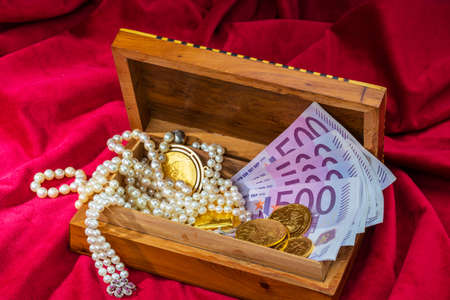 gold coins and bars with decorations on red velvet. symbol photo of wealth, luxury, wealth tax. photo