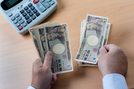 seem: japanese yen notes. hands counting money in japanese currency