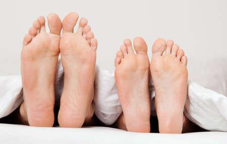 Dier ein paar Füße im Bett. Trennung und Scheidung