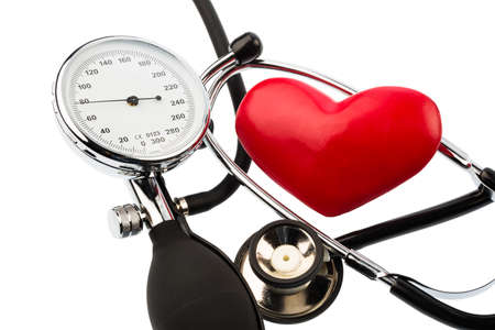 a sphygmomanometer, a heart and stethoscope lying on a white  Stock Photo