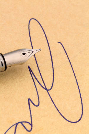 a signature and a fountain pen on yellow paper. symbol photo for contract testament and graphology
