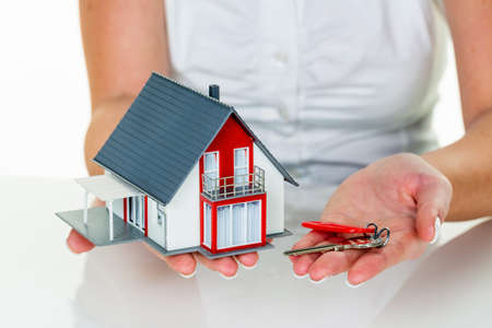 a broker for real estate with a house and a key. successful leasing and home sales by real estate agents. photo