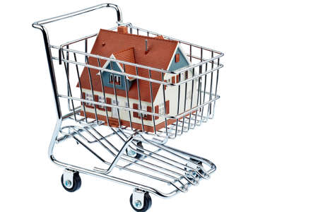 a model of a house in a shopping cart. symbol photo for home purchase.