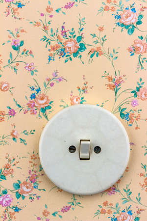 an old wallpaper with light switch. symbol photo for renewal and renovation. photo