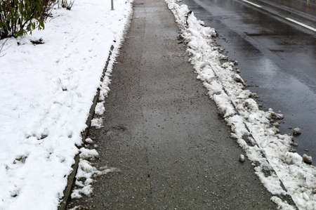 landowners: snow on sidewalk and street, symbol for accident risk and photo räumpflicht Stock Photo