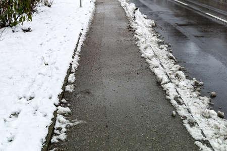 sidewalks: snow on sidewalk and street, symbol for accident risk and photo räumpflicht Stock Photo