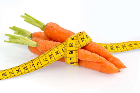 ideal: organically grown carrots with tape measure. fresh fruit and vegetables are always healthy. symbol photo for healthy diet.