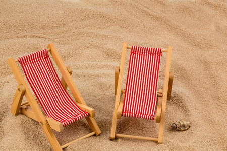 deck chair: a small deck chair (model) on a sandy beach. symbol photo for vacation, holiday, travel