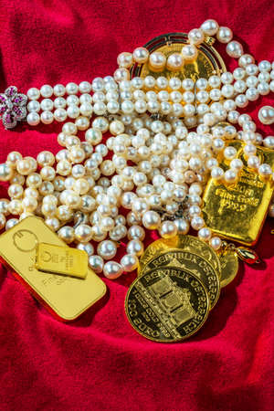 namacalny: gold coins and bars with decorations on red velvet. symbol photo of wealth, luxury, wealth tax.