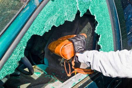 a thief stole a purse from a car through a broken side window. Standard-Bild
