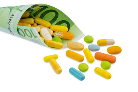 one hundred euro banknote: tablets and one hundred euro banknote symbolic photo: costs for medicine and drugs the pharmaceutical industry