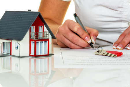 een vrouw tekent een koopovereenkomst voor een huis in een makelaar.