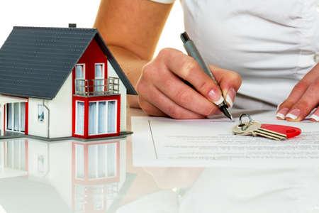 agente comercial: una mujer firma un contrato de compra de una casa en un agente de bienes raíces. Foto de archivo