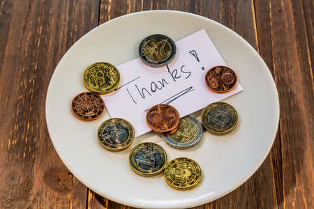 a plate of coins for tipping or charge for toilets. in english photo