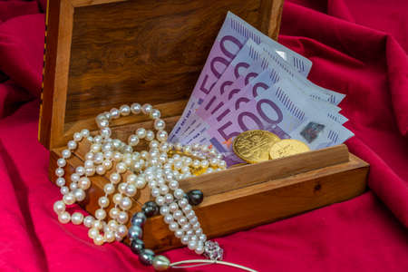 gold in coins and bars with decorations on red velvet. photo icon for wealth, luxury, wealth tax. photo