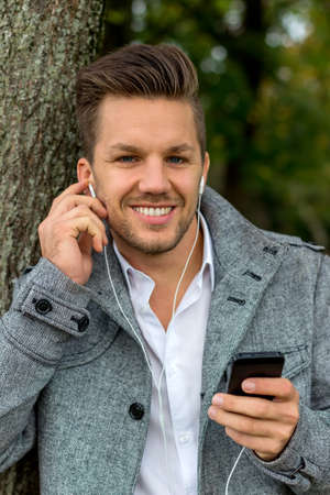 hark: a man listening to music on your mobile phone. talking on the mobile phone.