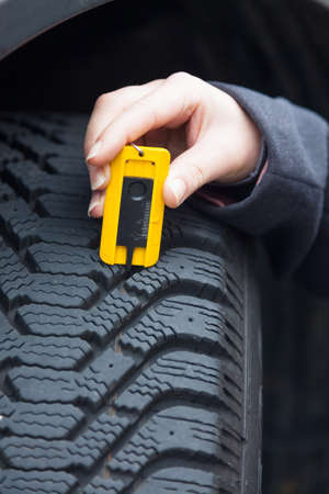 profile measurement: a young woman is measuring the tread depth of her car tire. the correct depth in the tread of a tire can prevent accidents. Stock Photo