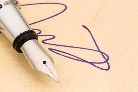 notieren: a signature and a fountain pen on yellow paper.  Stock Photo