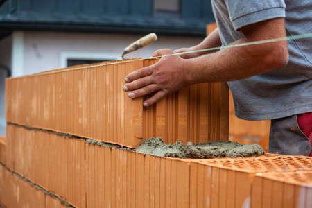 anoniem bouwvakker op een bouwplaats bij het bouwen van een huis bouwde een muur van bakstenen.
