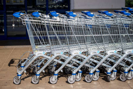 cheaper: in front of a supermarket shopping carts are ready for customers Stock Photo