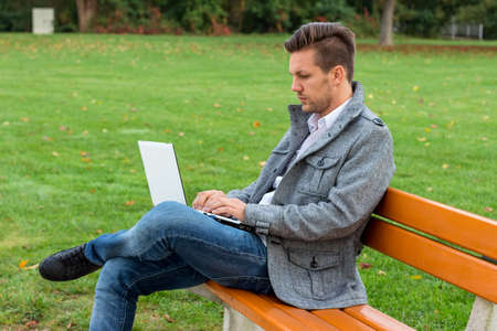 everywhere: a man with a laptop sitting on a park bench Stock Photo