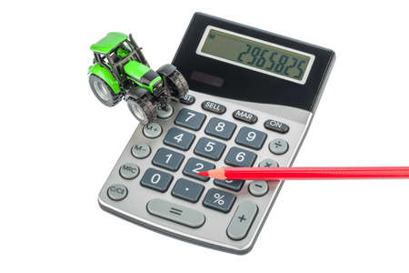 subsidy: a tractor and a red pen is on a calculator. cost of gasoline, wear and insurance. costs and subsidies in agriculture