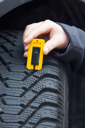 depth gauge: a young woman is measuring the tread depth of her car tire. the correct depth in the tread of a tire can prevent accidents. Stock Photo
