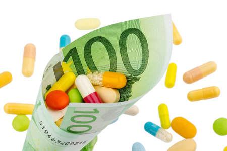 one hundred euro banknote: tabletas y ? 100 gastos de billetes Foto simb�lica para la medicina y los medicamentos de la industria farmac�utica Foto de archivo