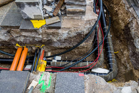 energy suppliers: at a construction site new lines for water, heating, district heating and electricity are fed. excavation with power lines Stock Photo