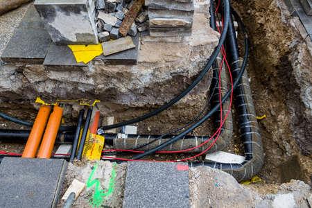 op een bouwplaats nieuwe lijnen voor water, verwarming, stadsverwarming en elektriciteit worden gevoed. opgraving met hoogspanningsleidingen