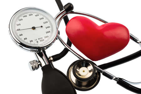 physican: a sphygmomanometer, a heart and stethoscope lying on a white background