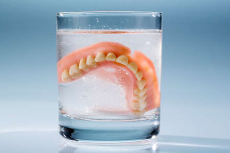 nursing class: a denture is cleaned in a glass with water. proper hygiene. Stock Photo