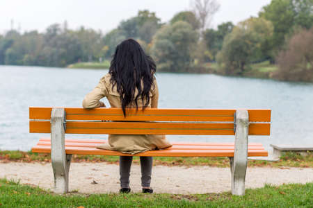 withdrawn: a young woman sitting on a park bench Stock Photo