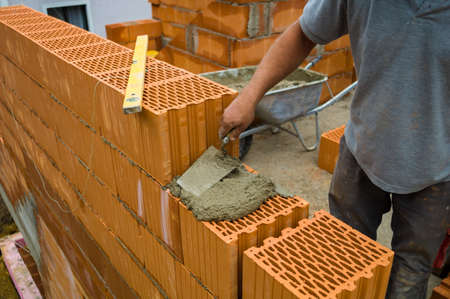 single familiy: anonymous construction worker on a building site when building a house built a wall of bricks. brick wall of a solid house. icon image for undeclared work and bungling Stock Photo
