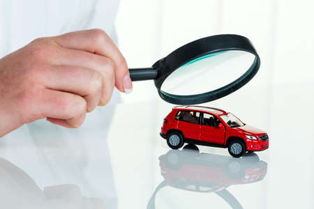 a model of a car is examined by a doctor. photo icon for workshop, service and car buying. Stock Photo