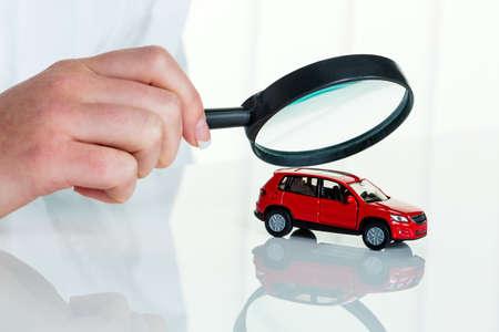 ein Modell eines Autos wird von einem Arzt untersucht. Foto Symbol für Werkstatt, Service und Autokauf.